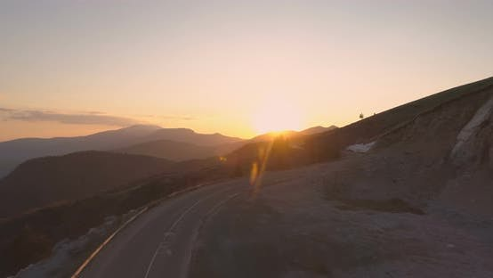 Drone Flying Towards Golden Sunset Following Winding Mountain Road