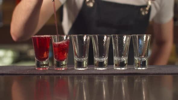 Thumbnail for Close Up, Bartender Pours Alcohol in Shot Glasses One By One