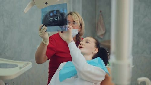 Dentist Carefully Looks at the Xray Picture with the Patient and Decides Which Teeth Should Be