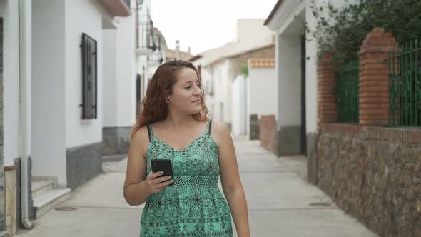 Thumbnail for Happy Woman Walking And Browsing Cellphone In The Street