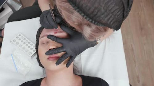 Slide Top View of the Eyebrow Tattoo Removal Procedure in a Beauty Salon