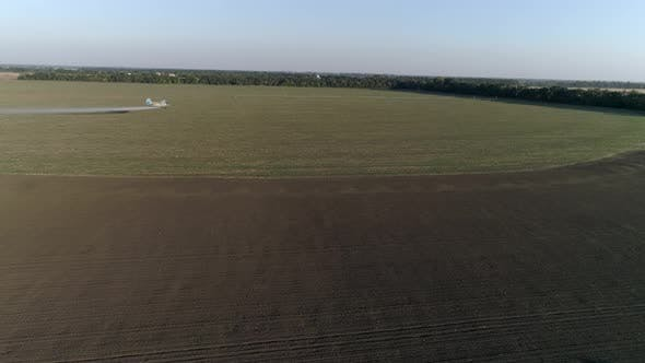 Thumbnail for Crop Duster Flies Over Field with Wheat and Splashing Chemicals Against Parasite in Drone View of