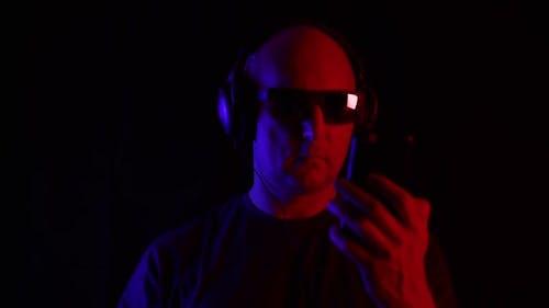 Bald Man Using Smartphone and Listening Music in Headphones in Studio