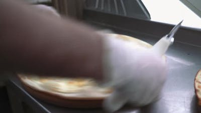 Cutting pizza on slices with special knife. Hand holding knife.