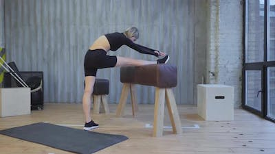 Athletic Woman Stretches Before A Gym Workout in a Bright Gym, Wearing a Black Top and Leggings