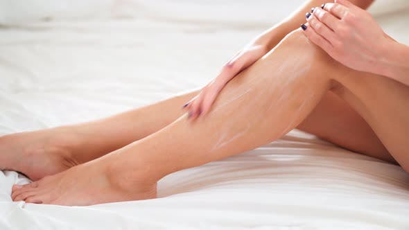 Moisturizer Cream on Her Slim Legs. Body Care and Cosmetic