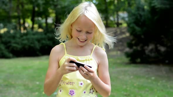 Thumbnail for Little Cute Girl Plays the Game on the Smartphone in the Park - She Moves with Phone