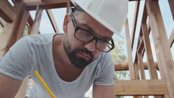Building Design: a Man in a Helmet Works, Camera Zooms Out