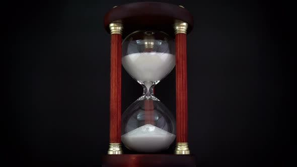 Cover Image for Rotating Hourglass On The Black Background.