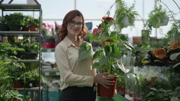 Thumbnail for Gardening, Portrait of Girl in Glasses with Decorative Home Plant in Hands in Greenhouse Background