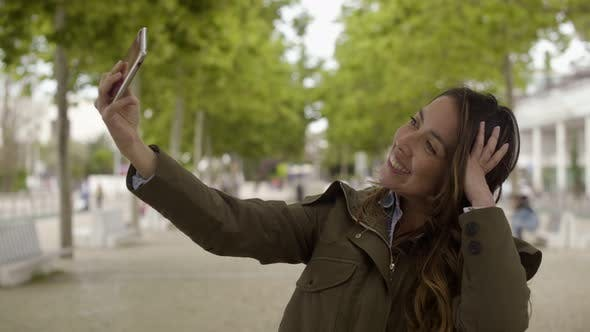 Thumbnail for Smiling Young Woman Taking Selfie with Smartphone Outdoor