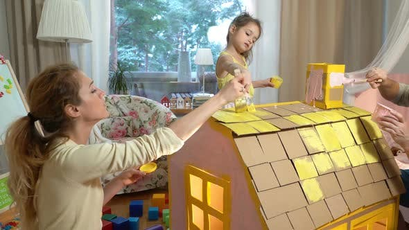 Thumbnail for Young Family with Child Building and Painting Toy Cardboard House Together.