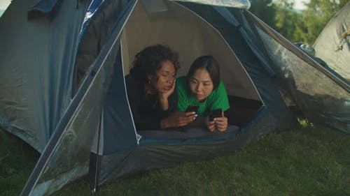 Lovely Multiracial Women Hikers Lying in Camping Tent Checking Photos on Phone on Mountain Hiking