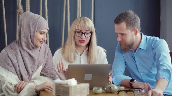 Thumbnail for Arab Woman and Caucasian Pair Are Talking and Watching on Laptop in Cafe