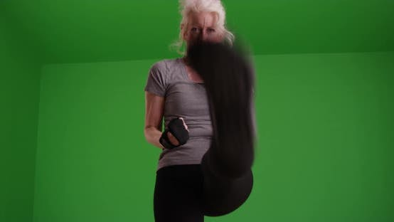 Thumbnail for Slow motion shot of focused mature woman shadowboxing on greenscreen
