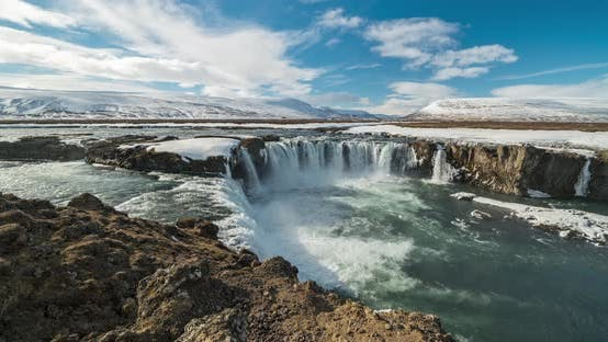 Thumbnail for Timelapse View of Godafoss Waterfall, Snowy Shore and River. Iceland in Early Spring