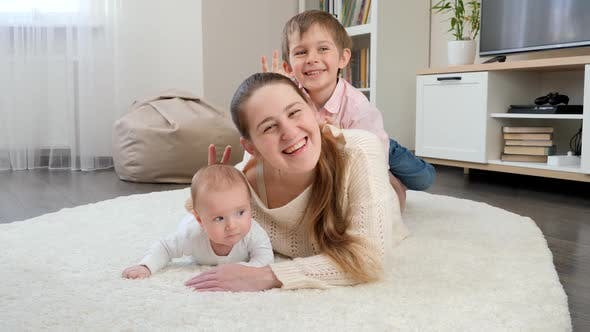 Funny Family Showing v Sign or Making Horns on Photograph in Living Room