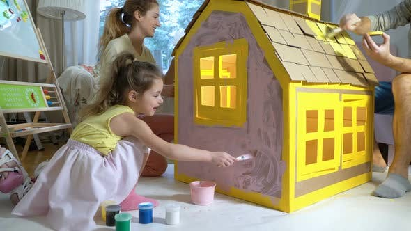 Thumbnail for Young Family with Child Building and Painting Toy Cardboard House Together