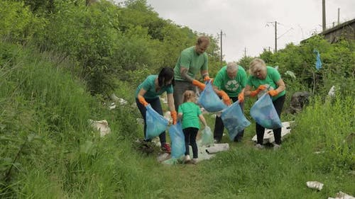 Team of Nature Activists in Eco T-shirts Picking Up Plastic Trash in Park. Recycle, Earth Pollution