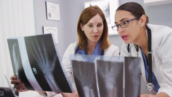 2 medical colleagues discussing x-rays of patients indoors office clinic