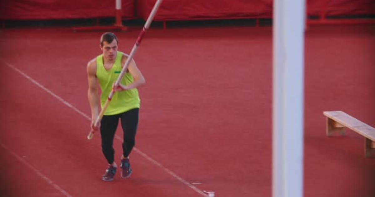 Pole Vault Training on the Stadium - an Athletic Man Performing His Jump Attempt