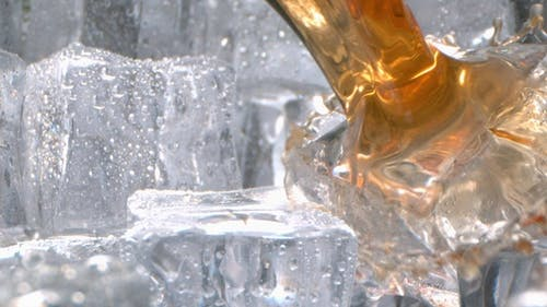 Liquor With Ice Pouring In A Glass In High Speed