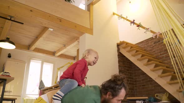 Thumbnail for Father playing with adorable infant son at the floor of living room.