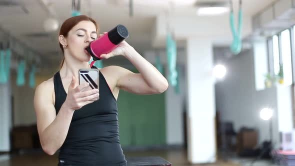 Fitness woman drinks water after a workout, fitness model rests in the gym