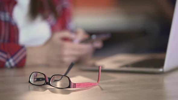 Thumbnail for Stylish Eyeglasses Lying on Table, Woman Texting on Smartphone, Communication