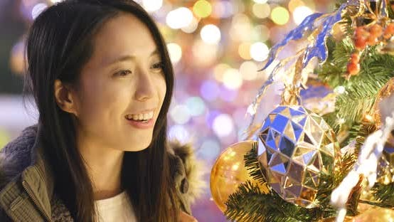 Thumbnail for Asian Woman looking at the christmas tree decoration