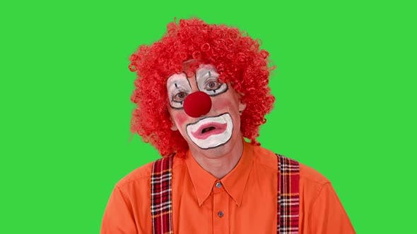 Clown with Unhappy Expression on His Face Walking in a Funny Way on a Green Screen Chroma Key