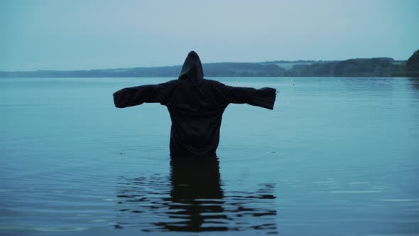 Thumbnail for Female figure in a black robe in the river