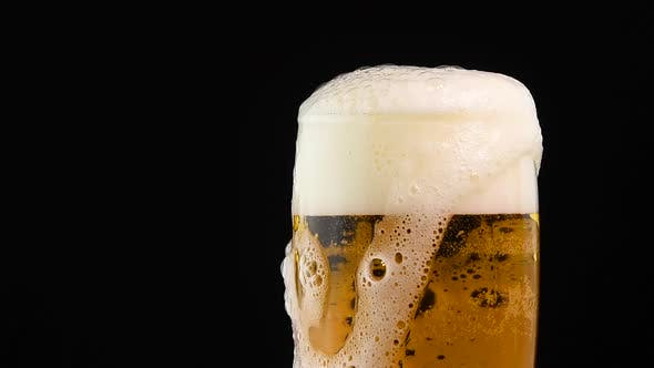 Pouring lager beer in big glass over black background