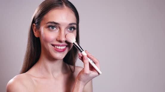 Cover Image for Beautiful Girl Doing Make Up with Brush