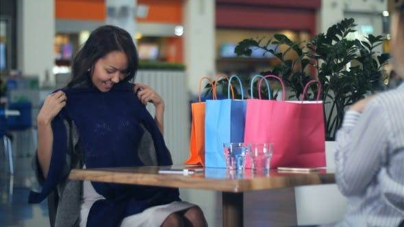 Cover Image for Happy Young Woman with Shopping Bags Showing New Clothes