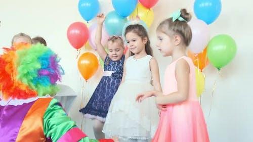 Lustiger Clown unterhält niedliche kleine Mädchen bei Geburtstagsparty