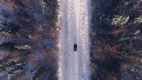 Thumbnail for Aerial view of a car driving in the snowy forest in Estonia.