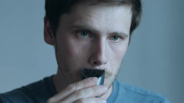 Man Shaving With Electric Razor.
