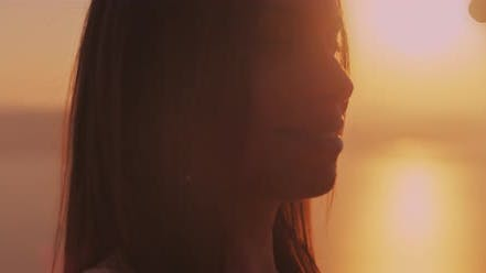 Thumbnail for Close up of a young couple looking at each other with love at sunset, with beautiful sun flare
