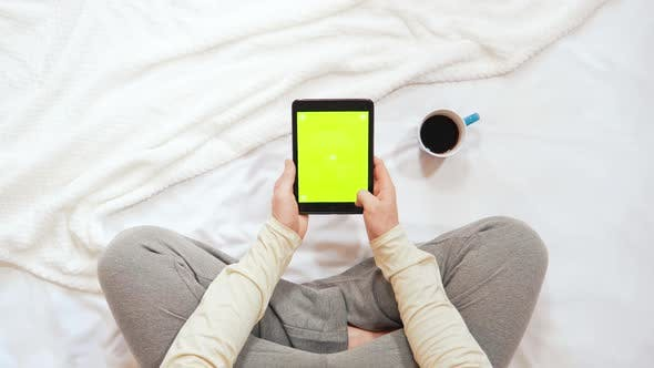 Thumbnail for Top View Man Sitting on the Bed Using Digital Tablet with Green Screen