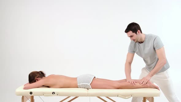 Male masseur with strong hands massaging lower part of leg to young woman lying on massage table