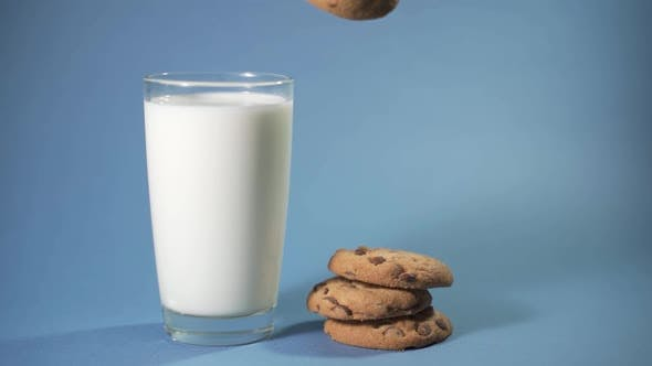 Woman Puts Chocolate Chip Cookies in a Glass with Milk
