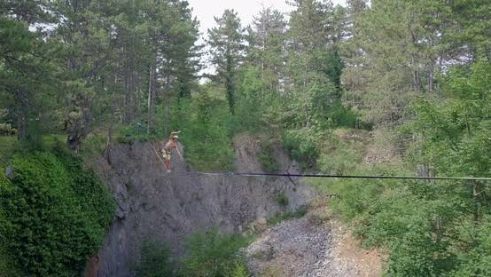 Thumbnail for A man tries to balance while slacklining on a tightrope