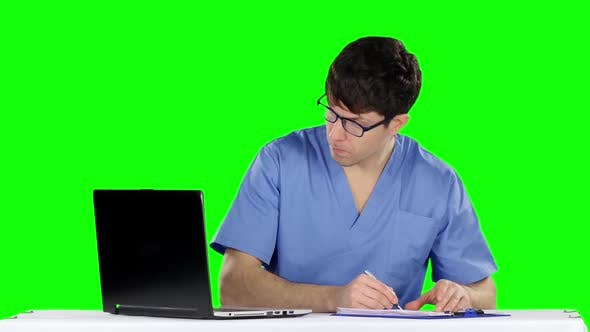 Cover Image for Male Doctor Writing at Desk in His Office Making Prescription. Green Screen