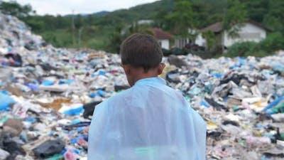 Back of Poverty Boy Walking on Garbage Dump