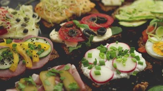 Verschiedene gesunde frische Sandwiches mit verschiedenen Gemüse, Kräutern und Zutaten auf dem dunklen Tisch