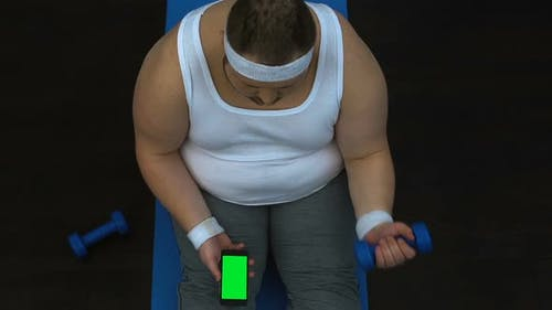 Obese Man Lifting Dumbbell and Watching Fitness Video Smartphone, Green Screen