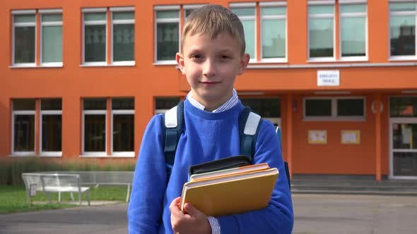 Thumbnail for A Young Boy Holds a Stack of Textbooks and Smiles at the Camera in Front of an Elementary School