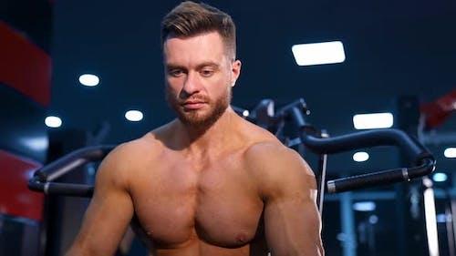 Gut aussehender Mann mit großen Muskeln, der im Fitnessstudio in die Kamera posiert.
