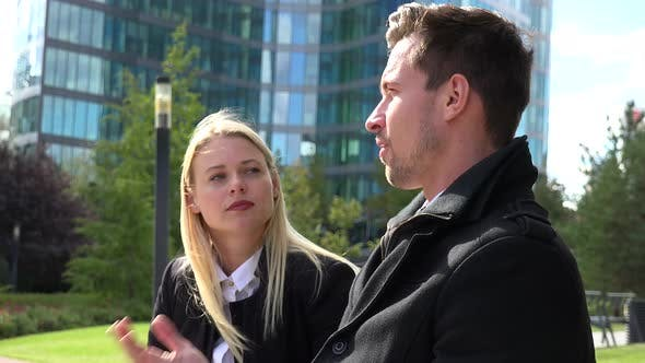 A Businessman and a Businesswoman Sit on a Bench and Talk in Front of an Office Building
